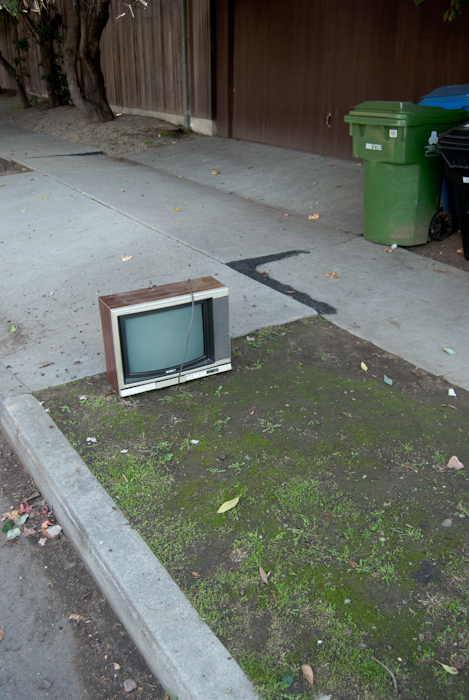 television at curb with trash cans