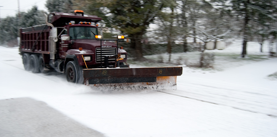 snow plow driving past trees