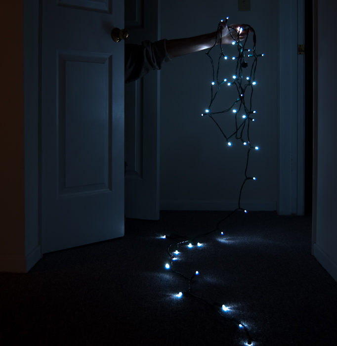 hand out from closet with Christmas lights