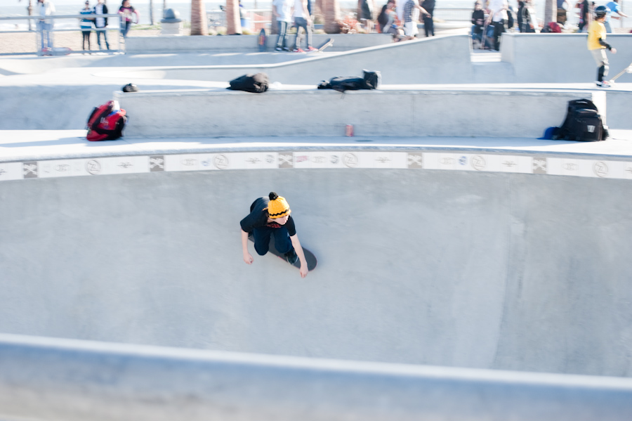 skateboarder moving along pit wall
