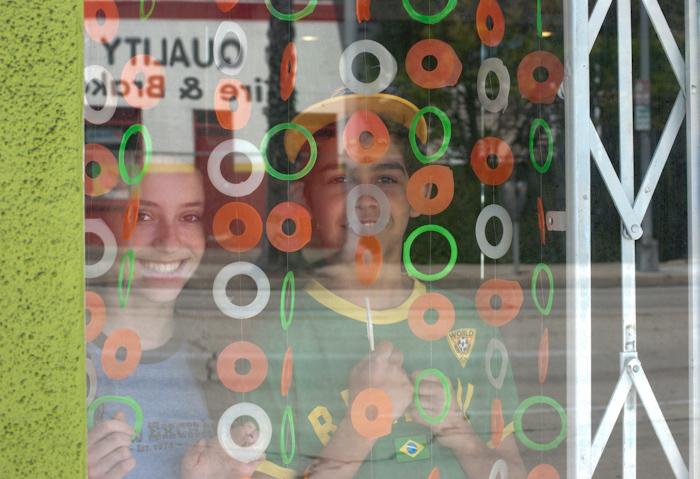 children in window behind curtain