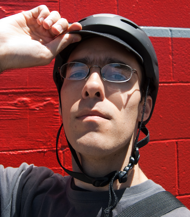 portrait in bike helmet against red wall