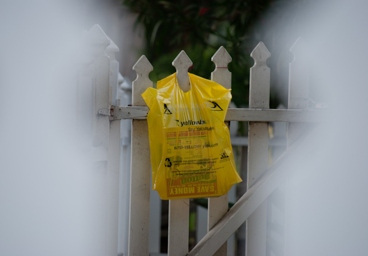 phone book in bag on picket fence