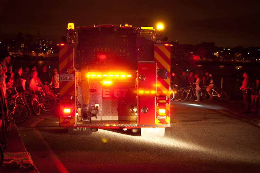 fire truck with red lights turning corner with bicyclists
