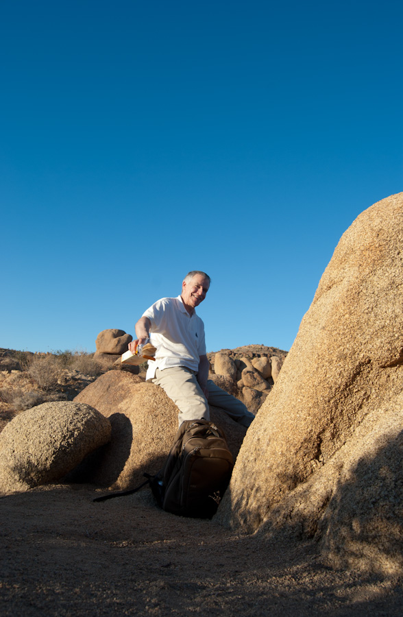James seated on rocks holding out crackers