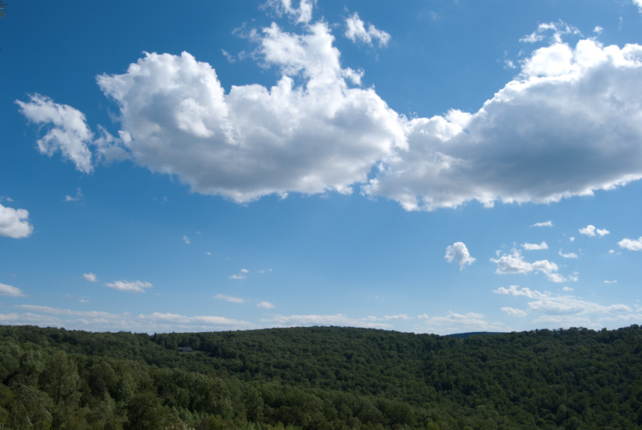 clouds over forested hills