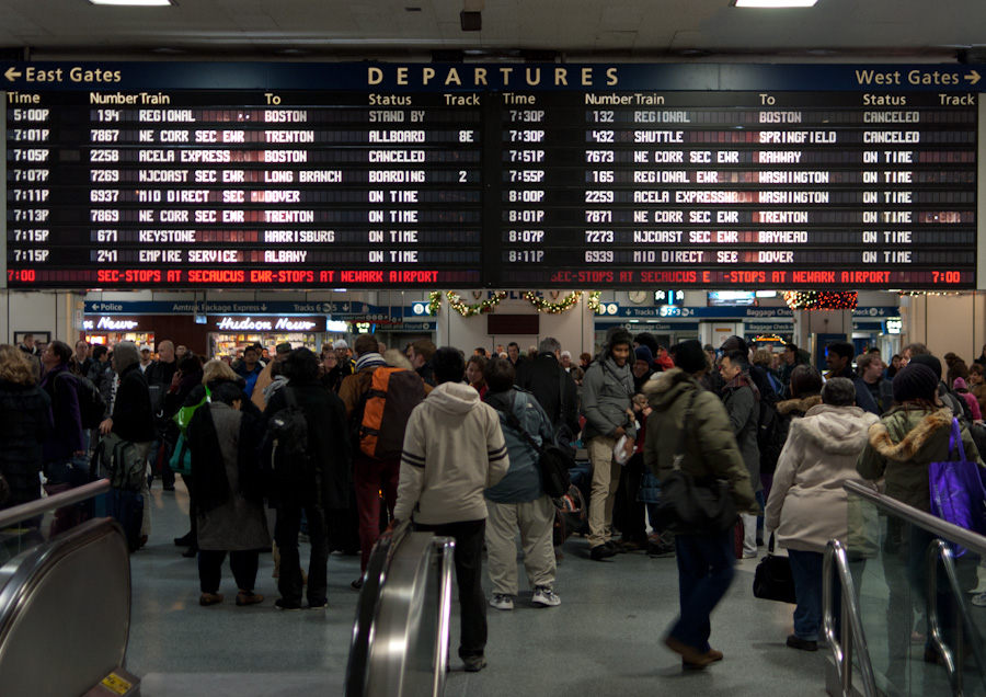 crowd below departure board in New York Penn Station