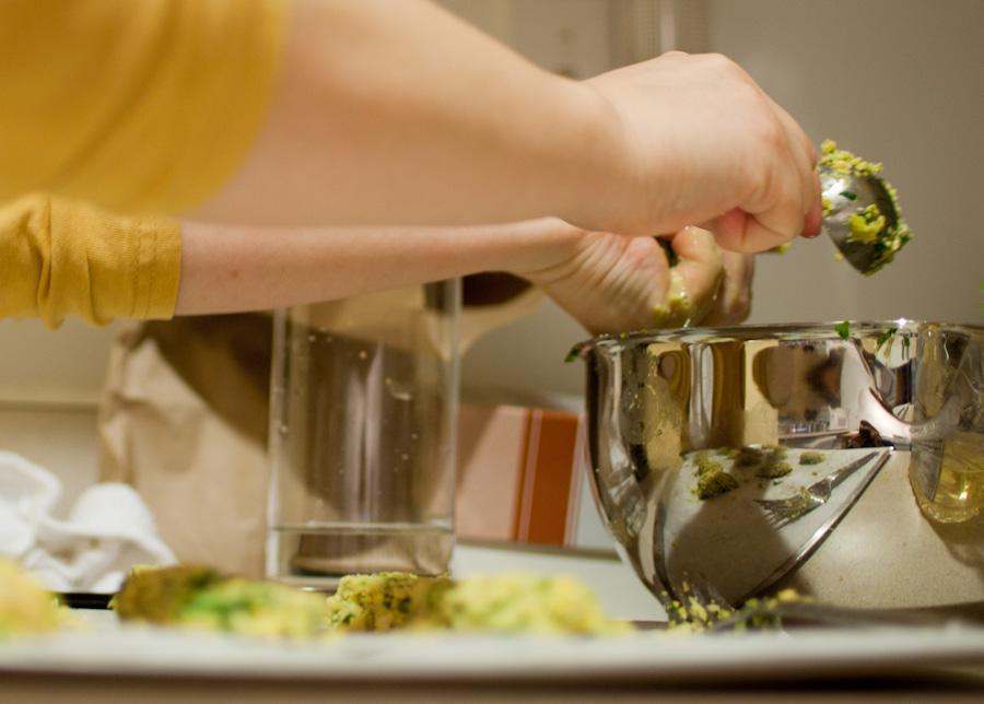 reflective bowl, hands, and falafel