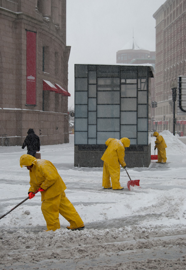 men in yellow, shoveling