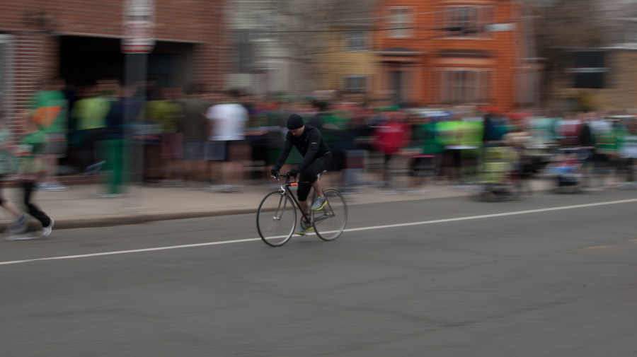 man riding past crowd