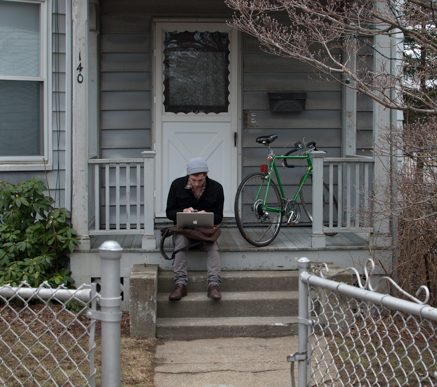 man on steps with laptop and bicycle