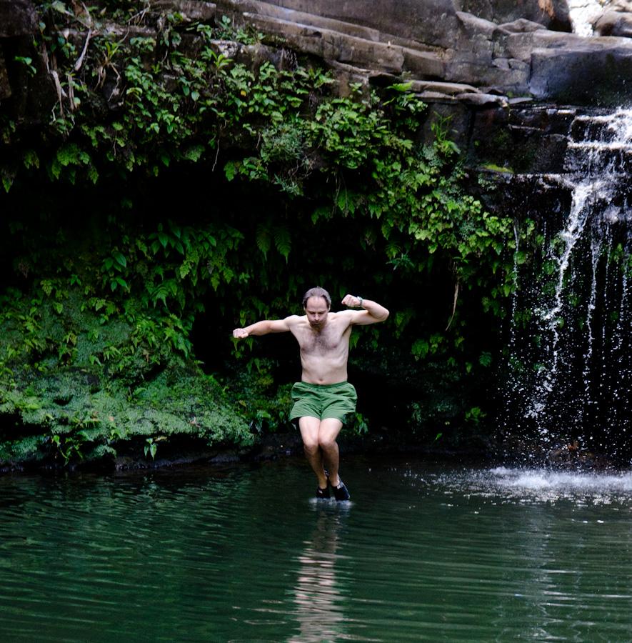 man jumping feet at water