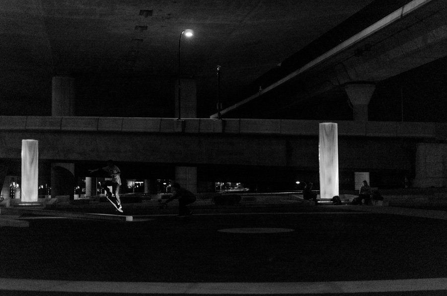 skateboarders under bridge, grayscale