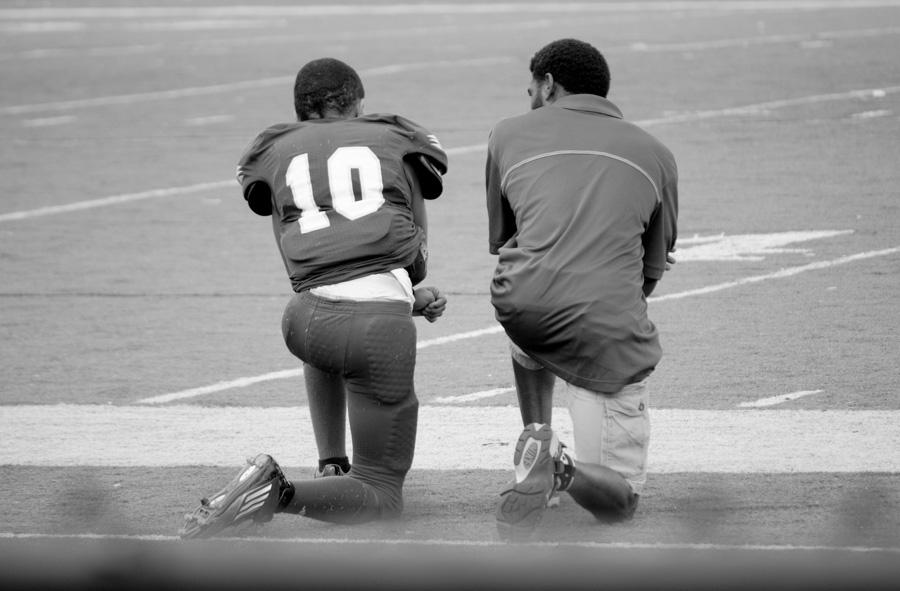 men kneeling at football game